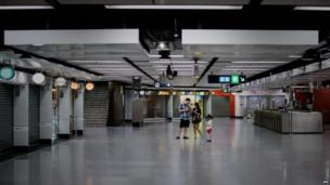 A man and a woman check a mobile phone in an empty subway station in Hong Kong on 14 August 2013, as people stayed home due to Typhoon Utor.