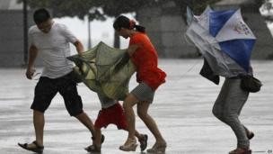 A family battle against the strong wind near the waterfront in Hong Kong, 14 August 2013