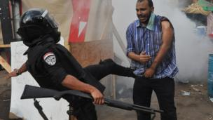 Policeman kicks supporter of ousted President Mohammed Morsi as they clear sit-in camp set up near Cairo University. 14 Aug 2013