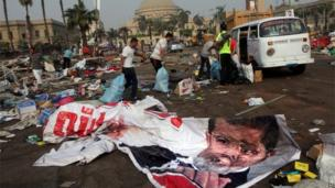Egyptians remove valuables they collected from debris in a protest camp next to a banner depicting Egypt's ousted President Mohammed Morsi in Nahda Square, 15 August