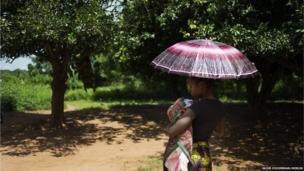 Chimene Kpakanale with her new baby sheltering under an umbrella in Obo, Central African Republic