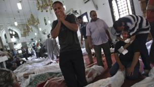 Men grieve over bodies on the floor of Cairo's Eman mosque, 15 August