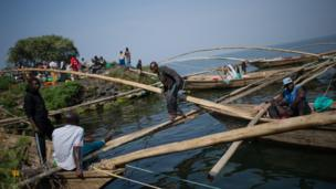 A fisherman walks between traditional wooden boats on the shore of Lake Kivu in Goma, in the east of the Democratic Republic of Congo - Sunday 11 August 2013