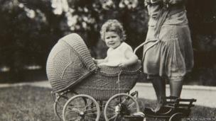 Previously unpublished family photograph issued by the Royal Collection of Queen Elizabeth II sitting in a wicker pram in 1928