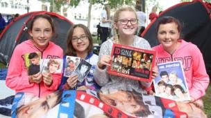 Four girls sit in front of their tent holding up One Direction merchandise.
