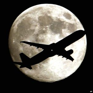 A jet on approach to Los Angeles International Airport flies in front of the Moon on 19 August 2013
