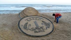 Indian sand artist Sudarsan Pattnaik puts the finishing touches to his sand sculpture of a rupee coin.