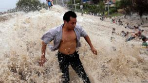 People struggle as waves from a tidal bore surge past a barrier on the banks of Qiantang River in Haining, Zhejiang province, 22 August, 2013.