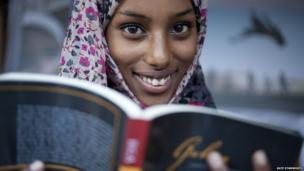 A book fair volunteer, Sumaya, reading Guban by New York writer Abdi Latif Ega - Hargeisa, Somaliland