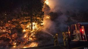 Firefighters hose down burning trees as the Rim Fire in California rages on, 25 August 2013