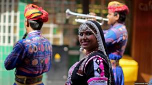 An Indian brass band play in the street, they are wearing brightly coloured clothes and a woman in smiling at the camera
