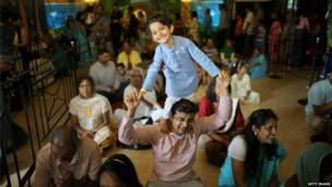 A young boy stands on his fathers shoulders as devotees pray inside the temple at the Janmashtami Hindu Festival at Bhaktivedanta Manor
