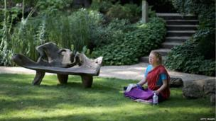 A devotee meditates in the George Harrison Memorial Garden during the Janmashtami Hindu Festival at Bhaktivedanta Manor