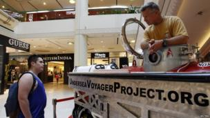 Scott Cassell in the mini submersible talking to a man in a shopping centre