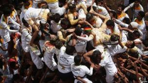 Devotees try to form a human pyramid as they struggle to break a clay pot containing butter during celebrations of Janmashtami in the Indian city of Mumbai