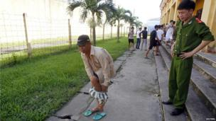 An ex-inmate takes off his jail uniform outside Hoang Tien prison (30 August 2013)