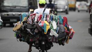 A man sells rubber flip-flops on his motorcycle in Manila, Philippines on 2 September 2013