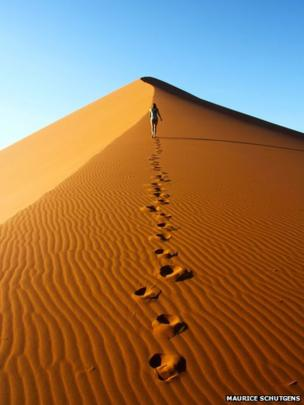 Woman walking on dune in Namib Desert