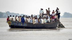 Flood-affected villagers use a boat as they navigate through the floodwaters of river Ganges and move to safer grounds, after heavy rains at Patna district in the eastern Indian state of Bihar
