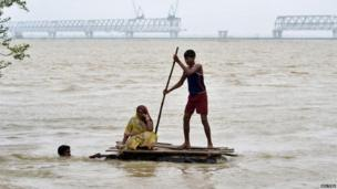 Flood-affected villagers use a temporary raft as they navigate through the floodwaters of river Ganges and move to safer grounds, after heavy rains at Patna district in the eastern Indian state of Bihar