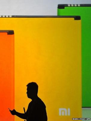 A man looks at his mobile phone as he walks past a screen during the launch of the new Xiaomi smartphone