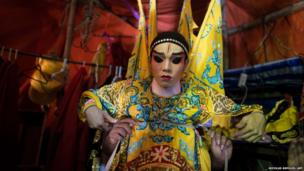 Chinese theatre performers put their costumes on before the show at a Chinese shrine in Bangkok