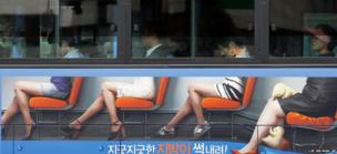 Passengers heads line up with figures contained in an advertisement on the side of the bus in Seoul, South Korea