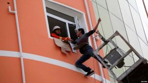 A firefighter tries to pull a worker into a window after he was trapped on a hanging platform