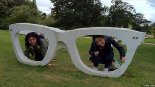 Two women pose inside an sculpture of a pair of glasses
