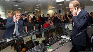 Prince William, Duke of Cambridge, and Prince Harry take part in a trade on at the BGC Partners trading floor during a charity day event