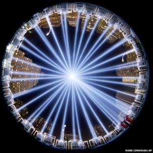 In a photograph made with a fisheye lens, the Tribute in Light rises above buildings in lower Manhattan