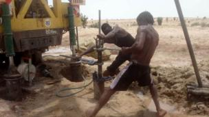 Technicians install a submersible pump in a borehole prior to test pumping, Turkana, Kenya