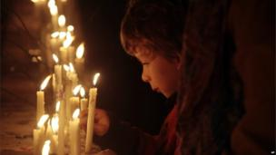 A boy lights a candle in the dressing rooms of the National Stadium during a candlelight vigil on 11 September, 2013