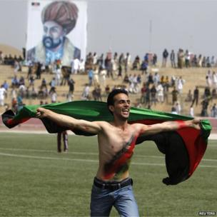 An Afghan football fan runs with the national flag as he celebrates their national football team's victory in the South Asian Football Federation Championship, at the Kabul stadium on 12 September 2013.