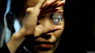 A Sotheby's employee holds the white diamond