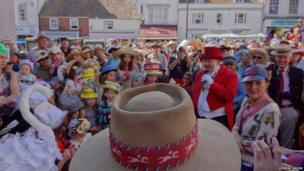 Hat Festival goers wear their hats, crowded around a ringmaster. Photo: Deirdre Snook