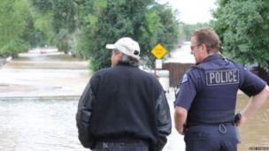 Policeman surveying the floodwater in Boulder, Colorado, US. Photo: Mike Dobson