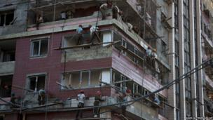 North Korean soldiers work on the side of a high rise building under construction in Pyongyang