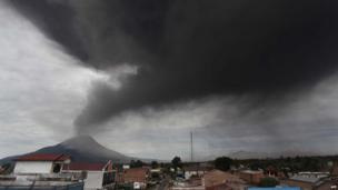 A cloud of ash rises from the crater of the Mount Sinabung volcano (back L) during a fresh eruption on 17 September, 2013, as seen from Karo district.