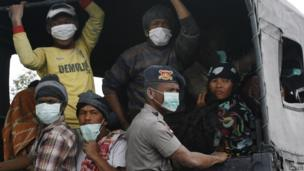 Villagers covered in ash sit on a truck while waiting to be evacuated to safety, as Mount Sinabung spews ash and hot lava during an eruption in Perteguhan village in Karo district, Indonesia's north Sumatra province, 17 September, 2013.