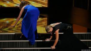 Actresses Tina Fey (left) and Amy Poehler stumble on stage