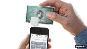 Square card reader plugged into mobile phone
