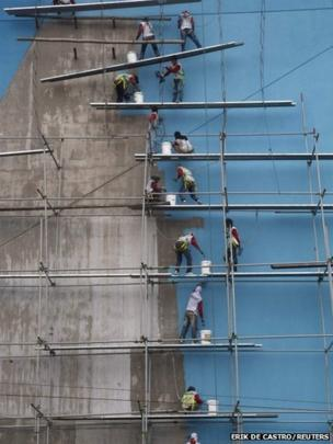 Workers paint a building in Manila