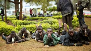 Street children watch media and others gather at a checkpoint near the Westgate Mall in Nairobi, Kenya, Wednesday 25 September 2013.