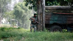 An Indian army soldier takes position during a rebel attack on an army camp in Samba