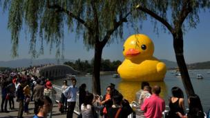 """Visitors view an 18-metre tall inflatable duck after its move to Lake Kunming at the historic Summer Palace in Beijing on September 26, 2013. The duck designed by Dutch artist Florentijn Hofman is to be displayed at Beijing""""s Garden Expo Park and the Summer Palace, from September to October as part of a world tour of 13 cities across 10 countries."""
