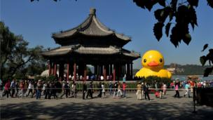 Visitors view an 18-metre tall inflatable duck after its move to Lake Kunming at the historic Summer Palace in Beijing on September 26, 2013.