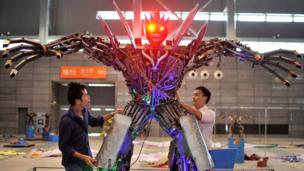 Workers test the functions of a giant robot as they set up a robot exhibition in Hefei, Anhui province September 26, 2013. The exhibition, which opens to public on September 28, will feature 38 robots which are made mainly from automobile components and range from 30 centimetres (11.8 inches) to 3 metres (9.8 ft) in height, local media reported.