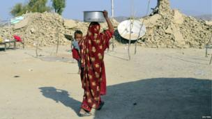 A survivor of an earthquake carries a pot on her head filled with drinking water as she walks near the rubble of a mud house after it collapsed following the quake at Dhall Bedi Peerander village in Awaran district, southwestern Pakistani province of Baluchistan, 27 September 2013