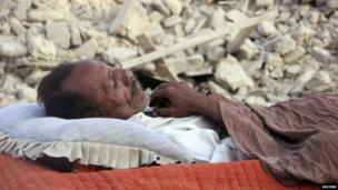 A survivor of an earthquake sleeps near the rubble of a mud house which collapsed following the quake in the town of Awaran, in the south-western Pakistani province of Baluchistan, 27 September 2013